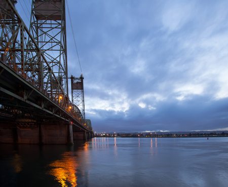 part of me: Lifting truss bridge with a lift towers across the Columbia River in Portland in the evening with the lights of the bridge reflected in the water. The bridge connects Oregon and Washington and is part of a interstate highway road I  5.