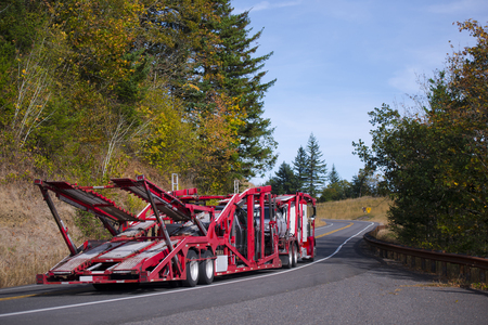 Big rig Semi Truck Car Hauler with red specialized trailer for transportation several cars moving on a winding crooked road with hills covered with yellowed autumn trees and evergreen fir trees.