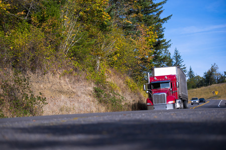 The classic model of a large modern red semi truck with a dry van trailer - excellent transport logistics business unit moving on a winding road with autumn trees in the warm sunlight day.
