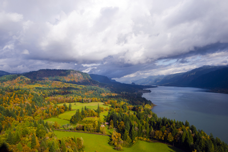 behold: Panorama of Columbia River Gorge Cape Lookout point of view landscaping floodplain with green meadows, autumn trees, lit by the rays of the sun and cloudy sky and the river, leaving the horizon.