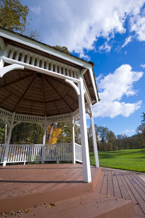 behold: Hexagonal arbour of wood with roof and supporting pillars and steps on an open meadow with green grass autumn trees and blue cloudy sky. The perfect place for a holiday or special events.