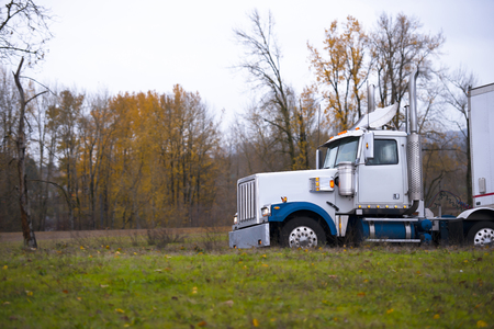 scenic drive: Large classic professional big rig semi truck with fancy roof spoiler and chrome details carries the trailer a scenic drive along the autumn yellowing trees. Powerful tractor for transportation of heavy loads. Stock Photo