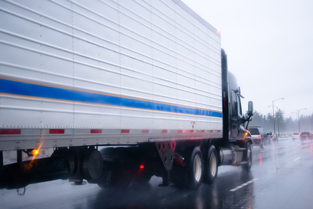 reefer: Big rig semi truck with refrigerator unit on reefer trailer transports commercial industrial cargo on a multi-lines highway with wet shiny coating and rain dust in rainy weather.