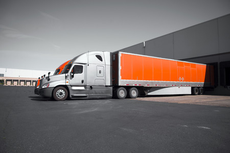 distances: Two modern professional commercial semi trucks in gray and orange with dry van trailers are standing in the dock on territory of the transport warehouses for loading or unloading of commercial cargo for transportation over long distances.
