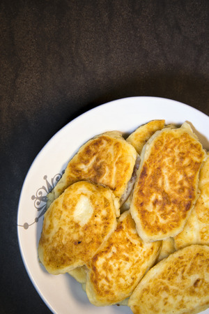 dietetics: Nutrient ruddy fried potato pancakes in the form of pastries laid out on a plate and ready to eat at the family dinner table. It refers to a handmade food and contains a lot of mineral and nutrients compounds for healthy organism. The dish is part of a po