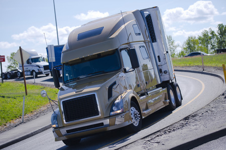 reefer: Modern powerful big rig semi truck with refrigerated trailer and the refrigeration unit on it, moving out in a circular exit from the highway in front of the other truck, moving from behind. Stock Photo