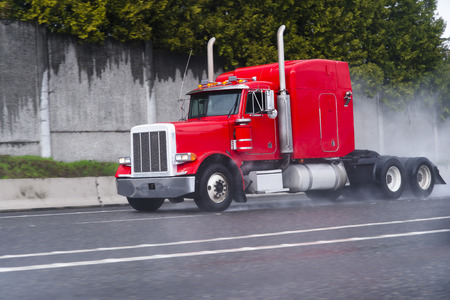 semitruck: Professional classical bonnet red semi-truck with a long cab and vertical exhaust pipes drive on highway with multiple lanes, raising by wheels a cloud of rain drops from the wet after rain road surface. Stock Photo