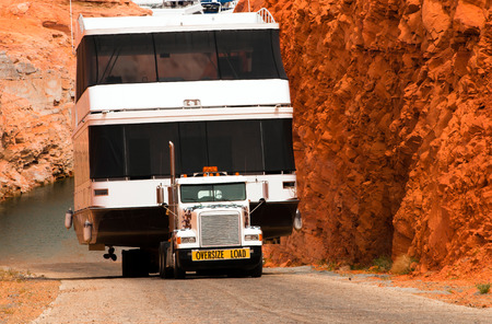 page arizona: The big powerful truck with a long trailer transports from Lake Powell huge houseboat ship going on a road between high red cliffs. The marine resort on the lake is located in the city of Page, Arizona.