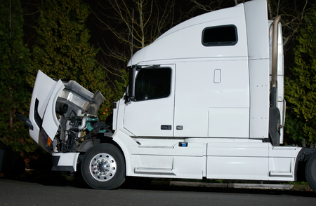 Powerful modern white semi-truck with the open hood standing evening on parking lot. The hot engine needs to be repaired and cooled by natural air flow for safety mechanic access. Stockfoto