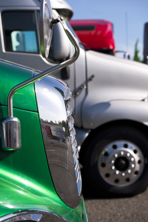 freightliner: Fragments of the trucks cab, including mirrors and chrome grille, with reflection in the mirror surface, standing in the parking lot waiting for the carriage of commercial cargo.