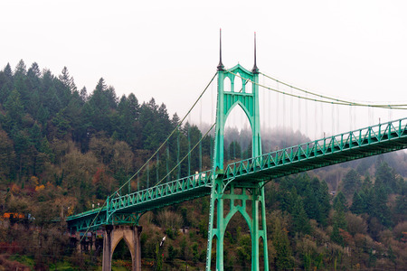 long johns: Unique and beautiful Gothic bridge with arches, spiers, towers and cable streamers spreading between the banks of Willamette River in the heart of the industrial area of Portland. Stock Photo