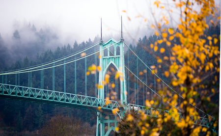long johns: Gothic style arches tracery St Johns bridge Portland Oregon in the morning mist decorated with autumnal yellowed trees. Stock Photo