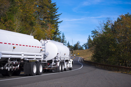White New Big Rig semi-truck with two tank trailers for transportation of fuels and chemicals move through the picturesque winding autumn road.