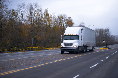 maneuvering: White Professional big rig semi-truck with a trailer moving on the road with autumn yellow leaves and the central dividing lines for maneuvering capabilities. Semi truck carry dry van trailer.