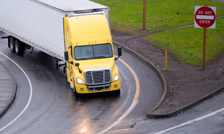 semitruck: Modern yellow big rig semi-truck with lights on with dry van trailer at the turn of the road highway exit on rainy wet road surface transports commercial goods over long distances in rain or shine, to make money. Stock Photo