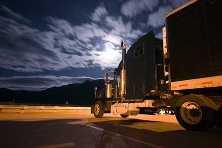 reefer: Colorful picture of a black semi truck and a reefer trailer standing in the parking lot at night, lit a lantern and moonlight through the transparent clouds.