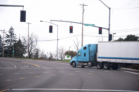 shipper: Big semi truck with a trailer for long haul at the turn of the road with traffic lights stopped at an intersection at a red traffic light.