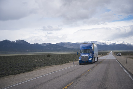 haul: The road stretches into the horizon on a flat plateau in Nevada moving blue semi truck with a dry van trailer transporting commercial goods.