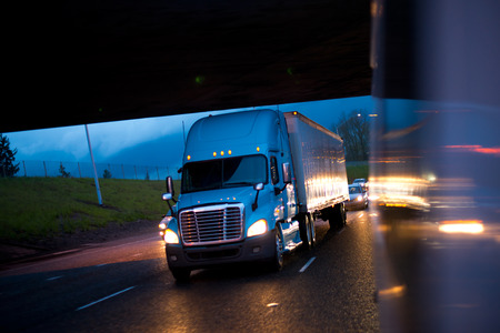 freightliner: Blue semi truck in the reflection of the evening headlights lights of car on a wet raining evening road.