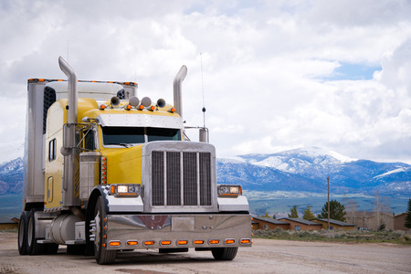 accents: Powerful yellow classic popular professional American bonneted big rig semi truck with chrome accents and a refrigerated trailer is parkedagainst the backdrop of snow-capped mountains, drowning in clouds. Stock Photo