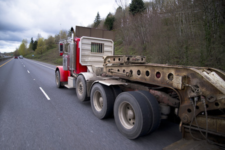 oversize load: Classic red semi truck with a flat bed trailer increased capacity for transportation of bulky oversized and heavy loads on a special step down lowered trailer. Stock Photo
