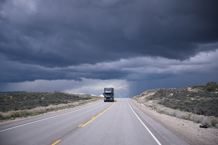 shipper: Dark gray semi truck with trailer approaching in the opposite lane level long road on the background of a stormy sky Nevada Stock Photo