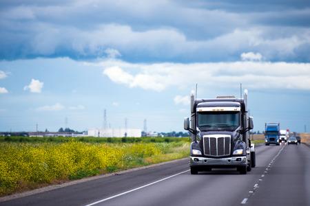 カリフォルニア州スプリング フィールドに沿って州間幹線道路で長距離専門の商業交通機関の暗い現代半トラック 写真素材
