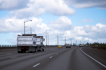 Professional semi truck with two self unloading trailers for bulk cargo for landscaping or building materials on the interstate road.