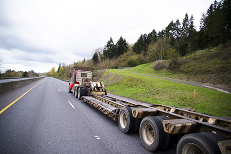 oversize load: Large classic powerful big rig semi truck with a trailer for transportation of oversized and heavy cargo and objects. Trailer with a step down for the transport of high loads. Semi truck drive on green highway in Washington. Stock Photo