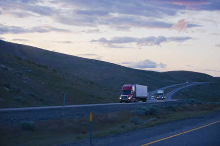 hurrying: Evening winding road in the hills of Columbia Gorge with moving semi trucks on the highway hurrying to complete the delivery before darkness.