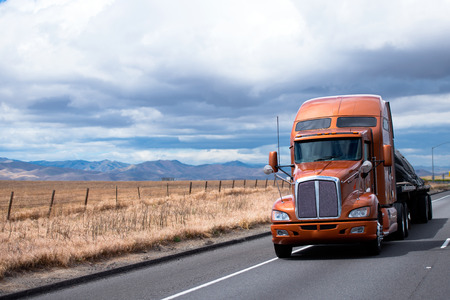 Stylish modern semi truck with a high cabin for the rest of the driver moving on the highway with a flat bed trailer, where the load is fixed by slings.