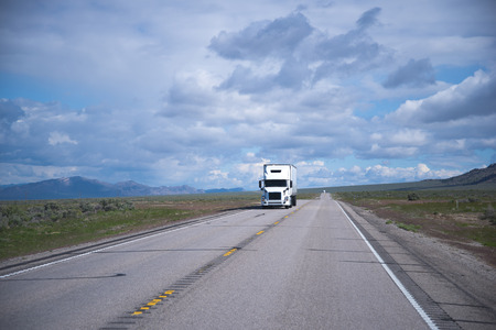 Popular model of white semi truck with a comfortable interior cabin for the professional long haul truck drivers transports cargo on a straight road going horizon with poor vegetation in Nevada