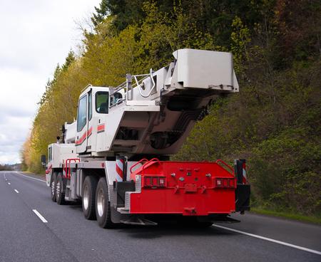 dislocation: Una enorme grúa móvil de gran alcance automotriz sobre ruedas con brazo extensible para levantar la construcción comercial y cargas industriales trasladado por carretera hasta el sitio de la próxima dislocación de trabajo.