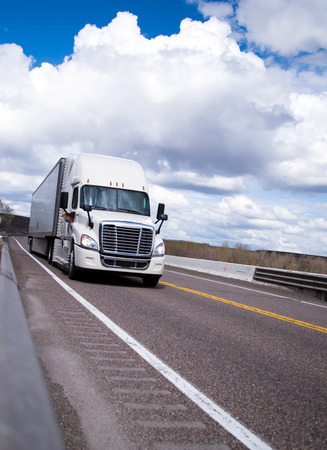 Classic modern new white big rig semi truck with a trailer moving on a smooth cloudy highway transporting a cargo of industrial products for livelihood all across America