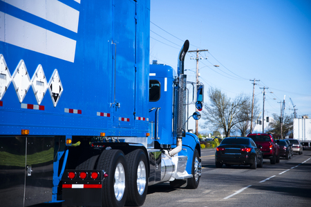 perishable: Spectacular bright blue big rig semi truck with a blue trailer with special tuning transports goods loaded on the road, moving in a stream of other cars