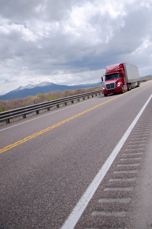 audible: Modern red semi truck with a trailer moving with a load on a flat straight road with a restrictive security fence on one side and grooves on the pavement for the audible warning.