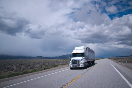 Single stylish professional commercial white big rig semi truck with refrigerated trailer carry cargo on a straight highway, going to infinity of dry prairie in Nevada