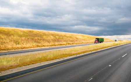 endless road: California landscape with endless road stripes and yellowed hills with grass, and semi trucks moving along the road and stormy gray cloudy sky Stock Photo