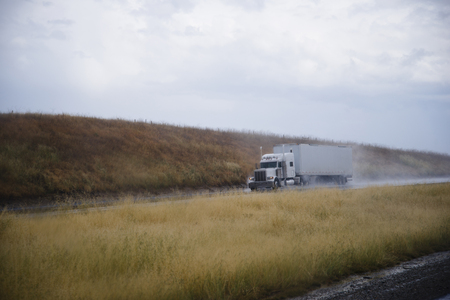 grass verge: Classic American semi truck with a trailer and high tailpipes moves with the load in the rain on the road among the hills with yellow grass, lifting by the wheels clouds of rain dust.