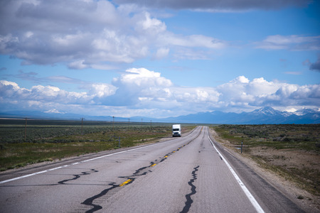 endless road: The view from the endless road endless plains, picturesque cloudy sky and a small semi truck standing on the roadside in Nevada waiting for the road service for troubleshooting of possible breakages.