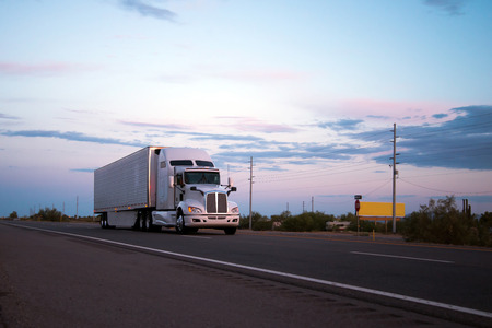The most popular model in the American big rig semi truck with a reefer trailer moving with cargo on the evening highway road in Arizona reflecting the last rays of the setting sun