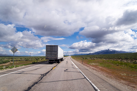 Landscape with a semi truck and trailer moving with commercial cargo along the old cracked road, resting against an endless horizon of Arizona prairies with sparse greenery and quaint floating clouds.