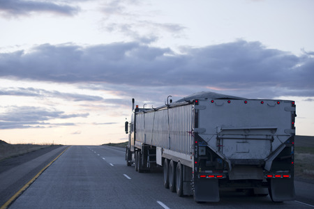 shipper: The long professional model in the American big rig semi truck with a two bulk trailers moving with cargo on the evening highway road in Arizona reflecting the last rays of the setting sun