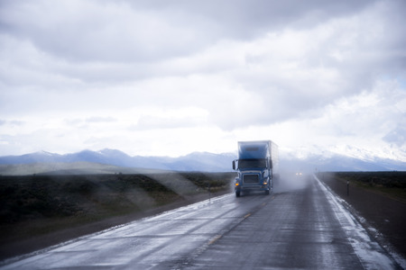 all weather: Semi Trucks Rigs carry and deliver loads in all weather conditions, including rain, on wet road in the rain clouds of dust, and in the reflected light from the raining road of headlights light. Stock Photo