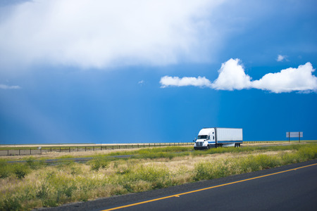 Pure transparent blue cloudy sky landscape, yellowed fields and roads with separate oncoming traffic lines and a white semi truck, as a worker hard ant in the middle of fields all pulls and pulls loads. Archivio Fotografico