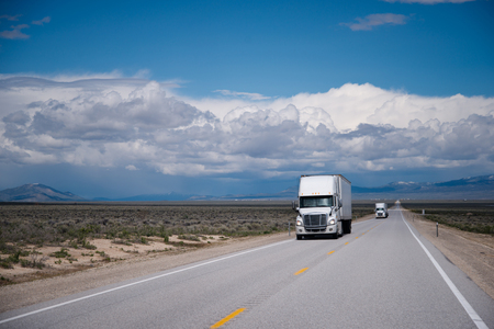 shipper: White semi trucks big rigs traveling on a commercial route for the correct delivery of goods across the prairies on the plateau of Nevada against the backdrop of an incredibly beautiful cloudy sky Stock Photo