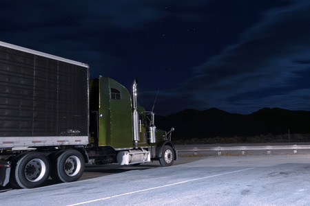 The popular classic American big rig semi truck with chrome details and a black trailer is standing at the fence in a parking lot in the moonlight on a background of dense dark night sky