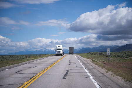 spellbinding: Two big rigs semi trucks are moving in the opposite direction on a straight flat road with a dividing strip transporting cargo in the endless prairies of Arizona against cloudy blue sky