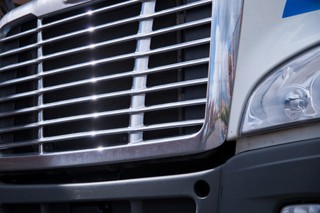 grille: Chrome grille bonnet American modern big rig semi truck with a reflection of the surrounding area and the glare of sunlight on the parallel strips of grille. Stock Photo