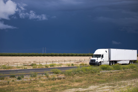 haul: Modern popular semi truck with cargo in the dry van trailer carrying out flight on delivery of goods to the customer on the interstate highway passing in the middle of fields in California against a dark stormy sky